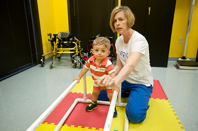 photo by Sarah A. Miller/Tyler Morning Telegraph  Epic Health Services physical therapist Lisa Williams has 15-month-old patient Cameron Halladay of Whitehouse practice walking at their Tyler clinic Wednesday.