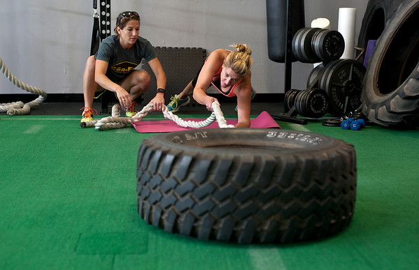 photo by Sarah A. Miller/Tyler Morning Telegraph  Cor-Fit gym owner Reagan Harris, left, leads client  Angela Bryant of Tyler in a tire pull exercise during a group workout class Tuesday June 24. Cor-Fit is a functional fitness studio located at 1721 S. Broadway, Suite B in Tyler.