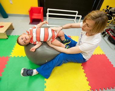 photo by Sarah A. Miller/Tyler Morning Telegraph  Epic Health Services physical therapist Lisa Williams works with 15-month-old patient Cameron Halladay of Whitehouse at their Tyler clinic Wednesday. Williams uses a large ball with patients to help them gain strength, balance and stability with their bodies.