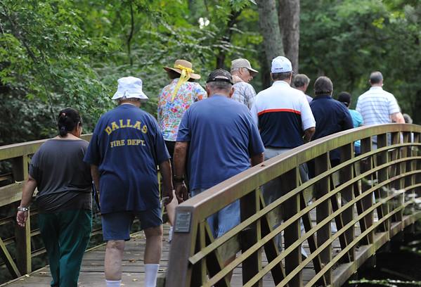 Walkers cross a bridge into the Rose Rudman Trail. (Victor Texcucano/Staff)