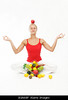 m316 CO8 / Choice 1 of 12 / B0A68P healthy lifestyle with fruits and yoga. Young blond woman with fruits and a red apple on her head