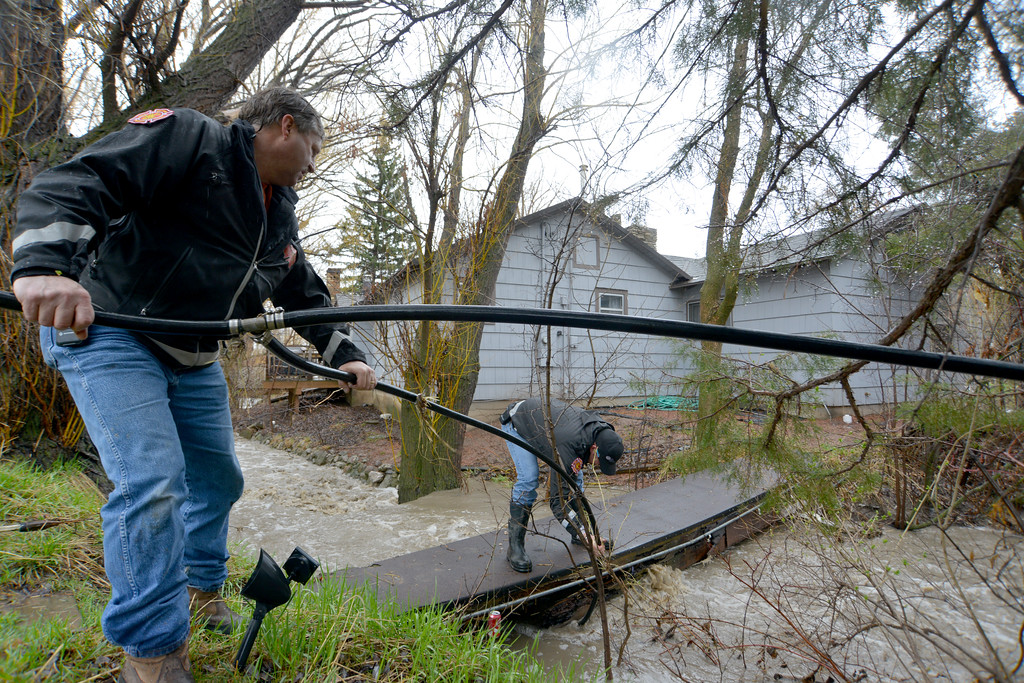 Justin Sheely | The Sheridan Press<br /> Big Horn Volunteer Fire Department firefighters Joel Wardell, back, and Chief Doug Enloe remove a water hose caught under a resident's footbridge over the Jackson Creek Friday afternoon in the town of Big Horn. Resident reported the flooding around 11 a.m. Friday morning after the water from the Jackson Creek began to flow over a culvert running under the intersection of 1st and High Streets near Big Horn School. Residents responded by filling sandbags to keep water from spilling into nearby homes. Big Horn Volunteer Fire Department responded by providing sandbags and clearing debris from culverts and drains. The National Weather Service has issued a flood advisory for parts of Sheridan County, which states that heavy rain and snow melt could lead to flooding along creeks and streams.
