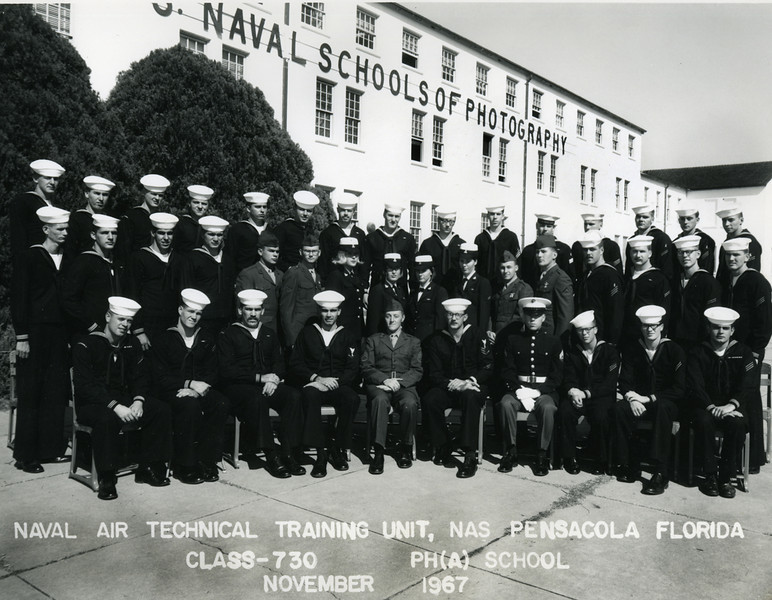 This is the graduation photo of my Naval School of Photography class 730. That's me seated in the front row on the far left. Surprising how few of the men's names I remember, but 1967, after all was a long time ago. First Class Petty Officer Easiley is our company commander. He's seated in the center between the two Marines. Petty Officer Fuller is forth from the left in front. Eldon Allison a good friend is standing in the back, fourth from the left. Our Patrol Squadron 46 would relieve Eldon's squadron in Cam Rahn Bay three years from this day. Eldon and I would cross paths many times when finally in the fleet.<br /> <br /> In the middle row standing fourth from the left is Honala Visser a wild Samoan who we all discovered was a man to avoid when he'd been drinking. One night, about the time this photo was taken, Visser clearly illustrated this fact. At a formal graduation party and for reasons no one would understand, Visser suddenly attacked Petty Officer Eaisley. Sailors were in dress blues and our wives were there all dressed in formal attire. Visser held the superior enlisted man in a headlock and refused to release his captive. The entire class tried to pull Hona off Eaisley, and he took on all comers with one free hand. Visser was able to send wave after wave of two to three men at a time crashing into the wall across the room. Visser would fling us off like King Kong swatting at biplanes. Eaisley was starting to pass out from lack of air when some of us struggled free the Visser's choking arm from our commander's neck. It took almost all the men in this photo to finally subdue Visser. While we all expected Visser to find himself in serious trouble for this display, Eaisley gave him a break and didn't press charges.