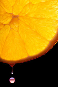 Macro orange slice lit from behind on a black background with a droplet falling.