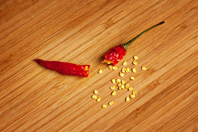 broken chili pepper spilling out seeds on a bamboo chopping board