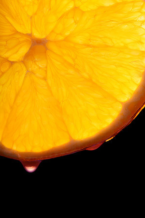A backlit, macro slice of orange with a drop of juice.