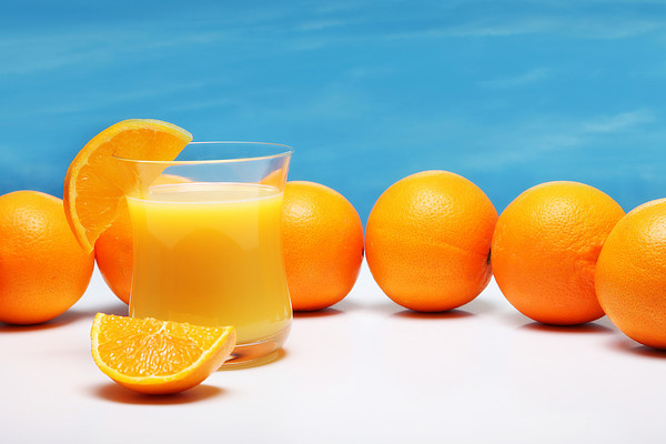 oranges and orange juice on a white table with a blue sky background