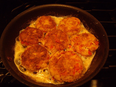 Crab cakes cooking in lots of butter.