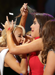 Miss Dogwood, Abby Lindsey, of Van Buren, right, reacts to getting her hair stuck in the crown of Miss Arkansas Savvy Shields at the end of the Pageant Saturday, July 9, 2016.