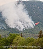 A small plane drops fire retardent on the lower edge of a forest fire; best viewed in the largest sizes