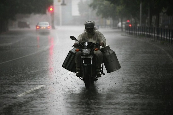 A milkman rides a motorcycle during heavy rain shower in the northern Indian city of Chandigarh August 19, 2012. REUTERS/Ajay Verma (INDIA - Tags: SOCIETY ENVIRONMENT)