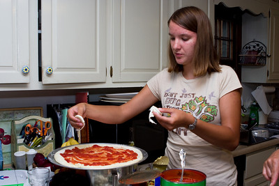 Gennie adding fresh mozzarella to pizza.