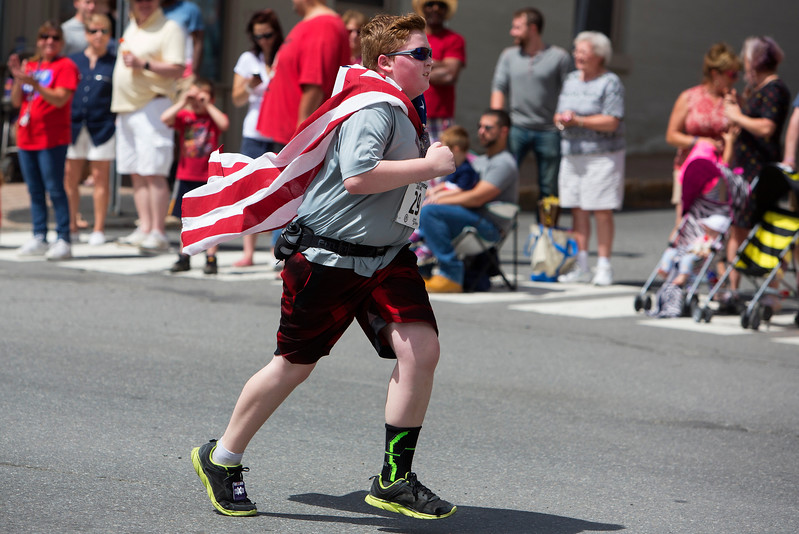 BANGOR, Maine -- 07/04/2017 - Jeremy Marks, 13, makes his way downtown while donning an American flag during the 37th Annual Walter Hunt 4th of July 3K road race from Brewer to Bangor Tuesday. Ashley L. Conti | BDN