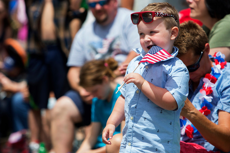 BANGOR, Maine -- 07/04/2017 - Brandon Heckenlivley, 3, takes a bite out of his flag during the annual Fourth of July parade from Brewer to downtown Bangor Tuesday. Ashley L. Conti | BDN