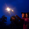 BREWER, Maine -- 07/04/2017 - Steve Garner (left), lights sparklers with daughter, Nicole Gardner, 9, near the Brewer Waterfront before the annual Kiwanis fireworks show over the Penobscot River Tuesday. Ashley L. Conti | BDN