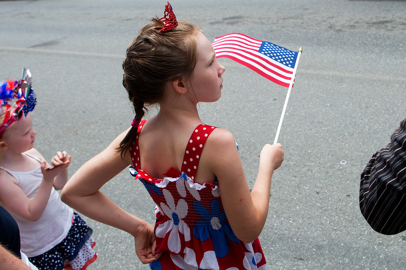 BANGOR, Maine -- 07/04/2017 - Shayla Henderson, 8, waves her flag during the annual Fourth of July parade from Brewer to downtown Bangor Tuesday. Ashley L. Conti | BDN