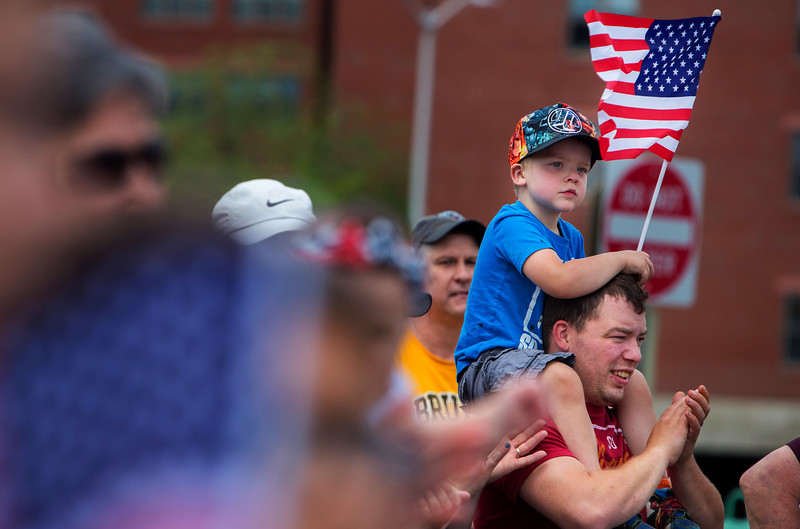 BANGOR, Maine -- 07/04/2017 - Raiden Lewis (left), 3, waves his flag while sitting on his father's, Jeff Lewis', shoulders during the annual Fourth of July parade from Brewer to downtown Bangor Tuesday. Ashley L. Conti | BDN