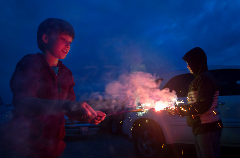 BREWER, Maine -- 07/04/2017 - Faith Brown (left), 11, and Caleb Gould, 12, play with sparklers near the Brewer Waterfront before the annual Kiwanis fireworks show over the Penobscot River Tuesday. Ashley L. Conti | BDN
