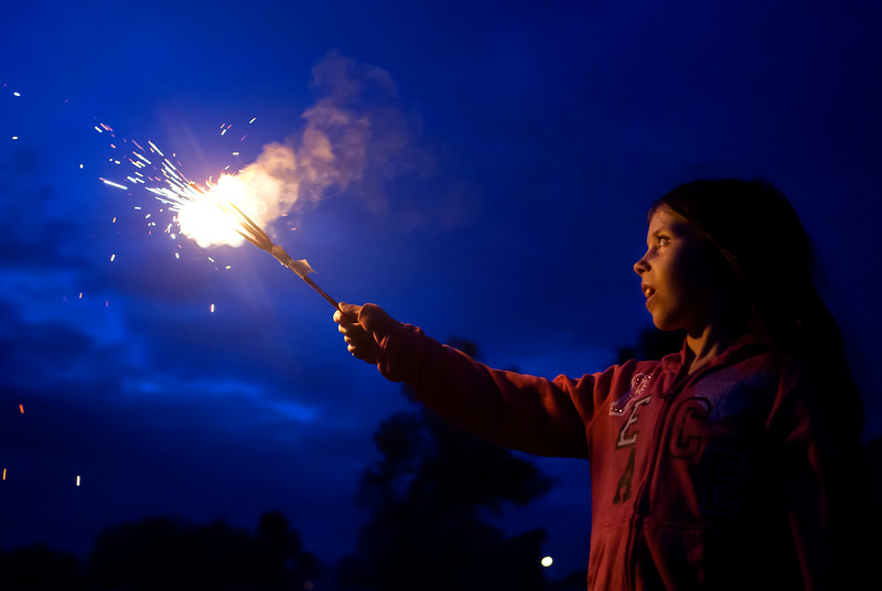 BREWER, Maine -- 07/04/2017 - Nicole Gardner, 9, watches her sparkler near the Brewer Waterfront before the annual Kiwanis fireworks show over the Penobscot River Tuesday. Ashley L. Conti | BDN