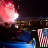 BREWER, Maine -- 07/04/2017 - An American flag is held while fireworks explode during the annual Kiwanis fireworks show over the Penobscot River near the Brewer Waterfront Tuesday. Ashley L. Conti | BDN