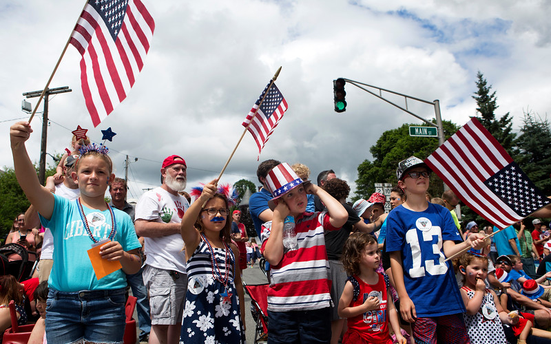 BANGOR, Maine -- 07/04/2017 - Josephine Jordan (from left), 10, Peyton Jordan, 8, Stephen Poplaski, 7, Hope Poplaski, 3, and Parker Jordan, 11, wave flags and watch the annual Fourth of July parade from Brewer to downtown Bangor Tuesday. Ashley L. Conti | BDN