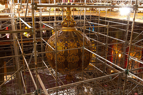The huge chandelier surrounded by scaffolding.