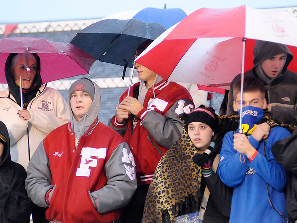 Frankton students huddle under umbrellas as they try to stay warm and dry as the Eagles hosted the Elwood Panthers on Friday.