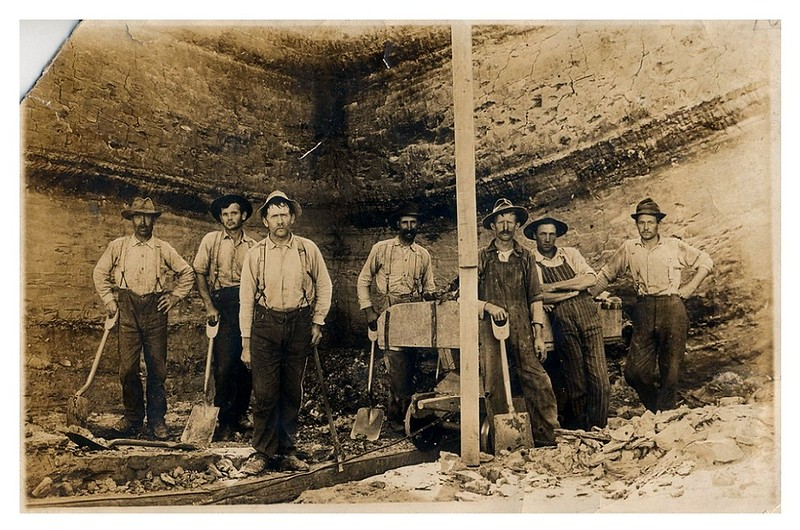 "(photo-aa) . . . Claus and fellow workers in clay pit.<br /> - Rita says Claus is the first man on the left.<br /> -- Scanned print size 4-1/4"" x 6-1/2"".<br /> --------------------------------<br /> Excerpt from: 'The Ghost Towns & Discontinued Post Offices of Goodhue County', by Roy W. Meyer, published 2003 ::<br /> 	"""" Claybank  ---  Goodhue County's clay industry, centered in the northern part of Goodhue township, has been economically important since its beginnings, early in the county's history. About 1861 a German-born potter, John Paul, bought some land in what came to be called the Clay Pits, installed a potter's wheel and a kiln, and began making crocks, jugs, bowls, jars, and small statues. After about ten years he moved away, but others followed.<br /> ---	In 1877 the Red Wing Stoneware Company began exploiting the deposits of clay that Paul had found so valuable. Six years later Minnesota Stoneware began to compete; North Star Stoneware came on the scene in 1892. In 1906 the three merged in the Red Wing Union Stoneware Company, which changed its name in 1936 to Red Wing Pottery. The company ended its manufacture of stoneware in 1967. Meanwhile, the Red Wing Sewer Pipe Company, organized in 1891 to exploit the inferior clay discarded by the stoneware companies, continued digging after the latter firms depleted the usable deposits. In 1949 the sewer-pipe company began reworking the clay pits that had lain closed since 1925. The pits finally closed in 1972.<br /> ---	Upon completion of the Duluth, Red Wing & Southern Railroad Company's line in 1889, the extensive clay-digging operations, underway for nearly three decades, expanded. Partly to serve the workers in the clay pits, Henry Holst built a store just east of the railroad track in section 5, in a narrow valley broadening farther north to form the valley of Hay Creek. ....<br /> ---	Claybank remained a busy place for many years. In the period of maximum activity at the clay pits, to which a branch line was built in 1892, some 75 men held jobs there. Two large boarding houses and several family residences provided housing. ....<br /> ---	After activity at the clay pits dwindled, the (Claybank) store depended on farmer patronage, which it solicited through a delivery system. """""