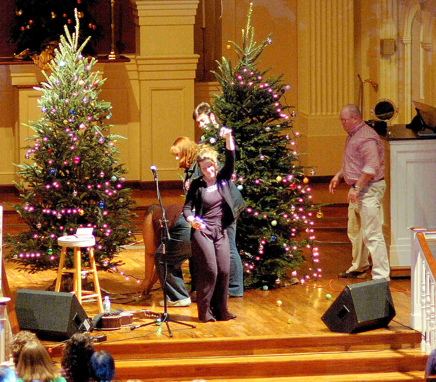 "That's Dar Williams, queen of the alt folk music community, breaking into an impromptu dance under a ""disco light.""  While singing her song ""The Ocean"" the tree on the right side fell forward, spilling the ornaments on the floor.  Dar is ""improvising.""  December 16, 2006 at the Westfield NJ Presbyterian Church."