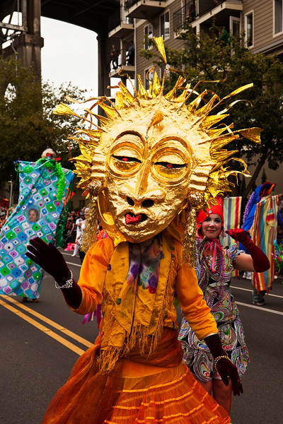 SEATTLE, WA - JUNE 16, 2012: A member of the Jaberwokey performance troupe wearing a gold sun mask in the annual Fremont Summer Solstice Parade in Seattle on June 16, 2012. The parade celebrates the start of summer on the Saturday on or immediately before the Solstice.