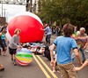 SEATTLE, WA - JUNE 16, 2012: The audience gets into the act as the giant balloon rolls over them on the street during the 2012 Annual Fremont Summer Solstice Parade in Seattle on June 16, 2012. The parade celebrates the start of summer.