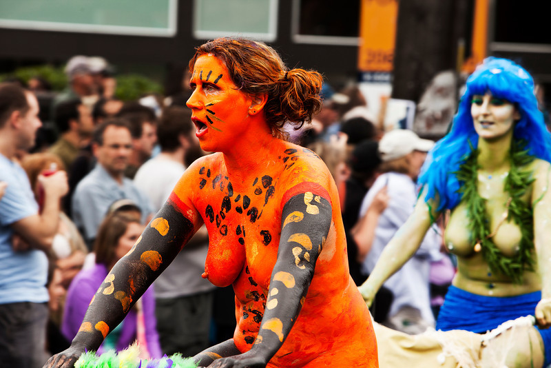 SEATTLE, WA - JUNE 16, 2012: An unidentified naked bicyclist in orange body paint participating in the annual Fremont Solstice Day Parade in Seattle on June 16, 2012. The parade celebrates the start of summer on the Saturday on or immediately before the Solstice.