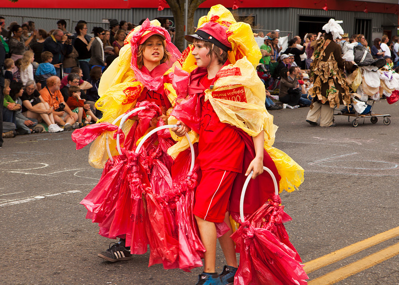 SEATTLE, WA - JUNE 16, 2012: Two young members of the Water Bottle Dragon performance ensemble marching in the annual Fremont Summer Solstice Parade on June 16, 2012 in Seattle. The parade celebrates the start of summer on the Saturday on or immediately before the Solstice.