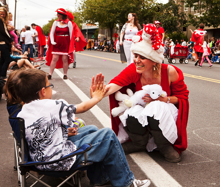 SEATTLE, WA - JUNE 16, 2012: A member of the Super Huggers performance ensemble giving a high-five to a spectator during the annual Fremont Summer Solstice Day Parade in Seattle on June 16, 2012. The parade celebrates the start of summer on the Saturday on or immediately before the Solstice.