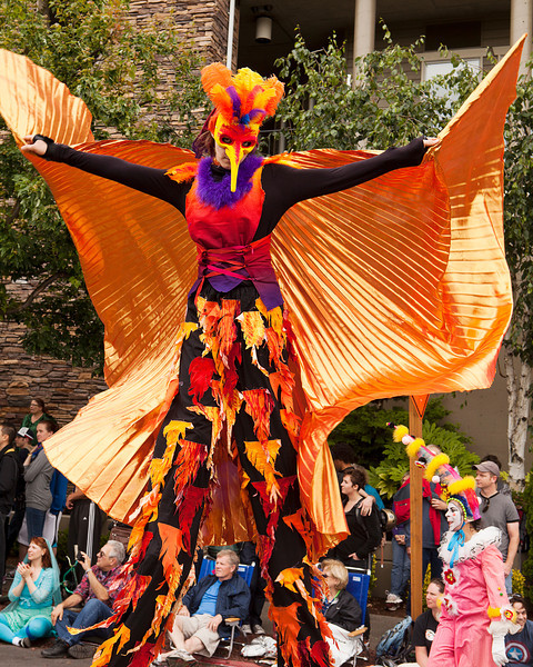 SEATTLE, WA - JUNE 16, 2012: A member of the Jaberwokey performance ensemble walking on stilts with a golden cape and a bird mask during the annual Fremont Summer Solstice parade in Seattle on June 16, 2012. The parade celebrates the start of summer on the Saturday on or immediately before the Solstice.