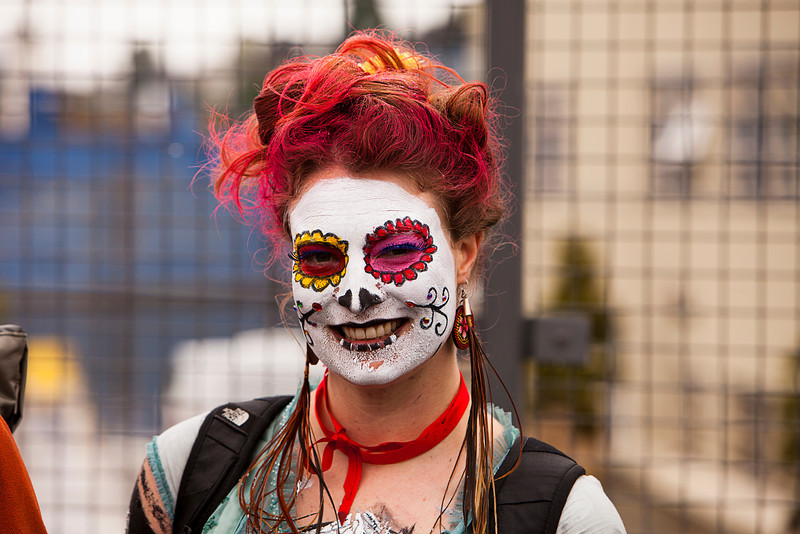 Seattle, Washington - June 18, 2011:  A spectator in full face paint and dyed hair watches during the 2011 Annual Fremont Summer Solstice Day Parade. The parade celebrates the summer solstice and features a number of alternative, non-traditional artistic ensembles.