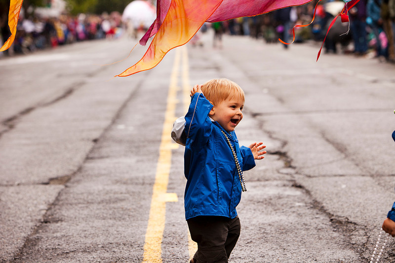 Seattle, Washington - June 18, 2011:  A small boy dancing under a banner on the parade route of the annual Fremont Solstice Day Parade. The parade celebrates the summer solstice.