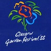 The official logo of the Glasgow Garden Festival. The slogan of the event was 'A Day Out of this World' <br /> <br /> The Glasgow Garden Festival was one of a number of events that took place in UK cities during the 1980s and 1990s. The Glasgow festival took place between April and September of 1988. The Festival was sited on former quays and dock basins on the south side of the River Clyde in the Cessnock / Govan areas of Glasgow. The area covered was that of the former General Terminus, Mavisbank Quay, Plantation Quay and the north, centre and south basins of the Princes Dock which had been reclaimed after the closure of the Dock in the late 1970s. Prior to the Garden Festival, these areas had lain largely derelict for a number of years. One objective of the festival was to instigate urban renewal programmes in the former docklands.<br /> <br /> The Garden Festival concept had begun in the German city of Essen in 1937. Others followed in Vienna, Nice, Nancy and Berlin. The Glasgow festival was the third of five held in the UK and, in visitor terms the most successful. When the gates closed at the Glasgow Autumn holiday in September a total of 4,345,820 had visited the event (over 1 million more than the next largest (Liverpool). However, the number was much lower than that attracted to the city's last big festival - The Empire Exhibition held in Glasgow's Bellahouston Park in 1938, which attracted over 13 million visitors.