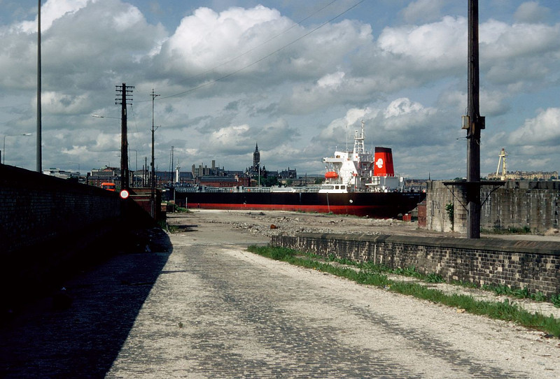 "This view is taken from the former West entrance to the Princes Dock. The new collier Sir Charles Parsons, one of three sister ships built by Govan Shipbuilders in 1985 was being moved from her builders fitting out basin to the No 3 Drydock for pre-trials hull inspection and cleaning. At this time she was entering the Princes Dock stern first to be aligned for stemming into the drydock which is on the left on the picture. <br /> <br /> The tower of the University of Glasgow is prominent in the background. The university has the oldest Chair of Naval Architecture in the world. The Elder Chair was established in memory of the pioneering shipbuilder John Elder, the founder of the Govan shipyard in which this vessel was built. See - <br /> <br />  <a href=""http://gdl.cdlr.strath.ac.uk/mlemen/mlemen031.htm"">http://gdl.cdlr.strath.ac.uk/mlemen/mlemen031.htm</a><br /> <br /> Sir Charles Parsons was built specifically to ship coal supplies into large coastal powers stations in England e.g. Kingsnorth. Hence, she carried the logo of the former Central Electricity Generating Board on her funnel. More details of the ship at:<br /> <br />  <a href=""http://www.clydesite.co.uk/clydebuilt/viewship.asp?id=634"">http://www.clydesite.co.uk/clydebuilt/viewship.asp?id=634</a>"