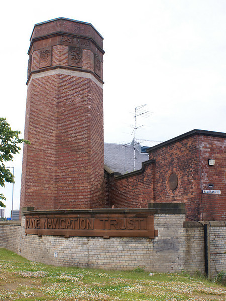 This tower is the remaining bottom section of the tall chimney that served the boilers of the hydraulic pumping station that was the buildings original purpose. When the octagonal brick chimney was demolished in the 1970s this section was retained as it contains the carved sculptures of the four winds that give the building its distinctive name. They are on the protrusion above the four rows of lighter coloured bricks that can be seen in this view.