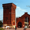One of the most recognisable buildings of Clydeside (though sadly in recent times becoming increasingly dwarfed and obscured by the high, modern  buildings constructed in close proximity). It is known as the 'Four Winds' Building (previously Pumphouse). During the Festival the building was active in two roles - the former boilerhouse - the tall bay on the right - served as the overnight depot for the five tramcars while the pumphouse - lower bay on the left was a pub / restaurant. <br /> <br /> The building was built to provide high pressure water to power the machinery in the former Princes Dock (cranes, capstans, etc.) Several coal-fired boilers  in the high bay on the right provided steam to power large pumps driven by huge reciprocating steam engines located in the lower bay. The pumps forced the fluid into a large accumulator (tank) that was housed in the big tower on the left. A heavy weight in the accumulator, acting under gravity, helped maintain the pressure at a sufficient level to drive the dock machinery, to which it was conveyed by a massive network of underground pipes. When the Princes Dock was new this power house was sufficient to serve the entire system but later, when additional equipment was installed - especially the coal wagon lift at the canting basin end of the dock - a second smaller pumphouse was installed at the west end of the Dock. <br /> <br /> Unfortunately, the impressive machinery inside the Four Winds Pumphouse was scrapped many years ago - what a magnificent visitor attraction it would have made nowadays. However, the Four Winds building is largely intact apart from the large red brick chimney that served the boilers. Most of it was demolished after the Pumphouse was taken out of service although the lower section, which has the symbols of the Four Winds carved into sandstone blocks, was retained. It is not visible in this view.
