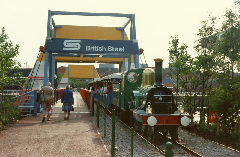 One of the Festival trains crosses the harbour bridge, a temporary bridge sponsored by British Steel plc. It connected Plantation Quay  to the west wall of the canting basin. It was constructed off site and floated into position. When a vessel required passage to or from the basin the bridge was floated out of the way then re-installed.