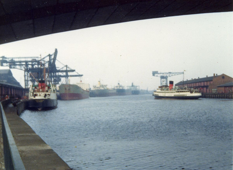 "A view looking downriver from Windmillcroft Quay in 1976. The Caledonian MacBrayne excursion turbine steamer Queen Mary has just departed from her berth at Anderston Quay. She had just resumed services from Glasgow following a gap of 6 years but by this time her traditional berth at Bridge Wharf had closed and she shared Anderston Quay with the paddle steamer Waverley.<br /> <br /> The nearest vessel on the left is the David MacBrayne cargo vessel Loch Carron at Springfield Quay. She operated cargo services to the Western Isles. Until the 1960s a fleet of such vessels were operated by MacBraynes from the Kingston Dock. Howeever, the traffic was diminishing and Kingston Dock was closed and filled in to enable the construction of the Kingston Bridge and M8 motorway. The services from Springfield Quay lasted for only a short time. Formerly Springfield Quay had been used for services to Burma and France and the following link picture shows the quay when it still had its complement of cargo handling cranes (one of the cranes in the Kingston Dock can also be seen in the distance) :<br /> <br />  <a href=""http://www.mitchelllibrary.org/virtualmitchell/image.php?i=14351&r=2&t=4&x=1"">http://www.mitchelllibrary.org/virtualmitchell/image.php?i=14351&r=2&t=4&x=1</a><br /> <br /> They can also be seen in the distance in the following mid-1950s view from the Stobcross Crane when the General Terminus unloaders were being constructed<br /> <br />  <a href=""http://www.mitchelllibrary.org/virtualmitchell/image.php?i=14554&r=2&t=4&x=1"">http://www.mitchelllibrary.org/virtualmitchell/image.php?i=14554&r=2&t=4&x=1</a><br /> <br /> Above, an ore carrier is being unloaded at General Terminus and three large ocean going vessels are laid up at Mavisbank and Plantation Quays (now Pacific Quay) in the distance."