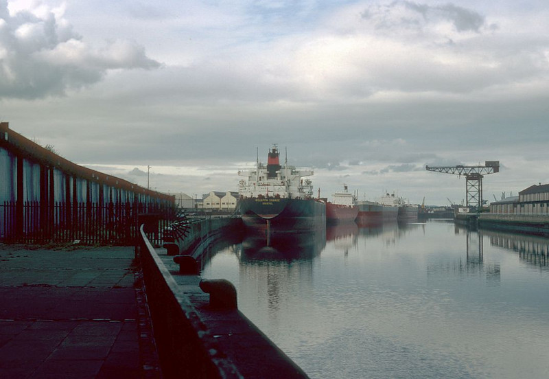 In the early 1980s after the closure of most berths upstream of Yorkhill to regular shipping the whole length of quay wall from Berth No 37 at General Terminus to Berth No 83 at Plantation Quay was utilised for laid up merchant ships. The vessels that berthed in Glasgow Harbour at that time were generally much larger than those that had operated from the port and was possible because all of the vessels were light. In this view the Rounton Grange is the nearest vessel berthed at General Terminus with the red hulled Grand Encounter and the grey hulled Greek-registered sister ships Thetis and Melete at Mavisbank/Plantation.