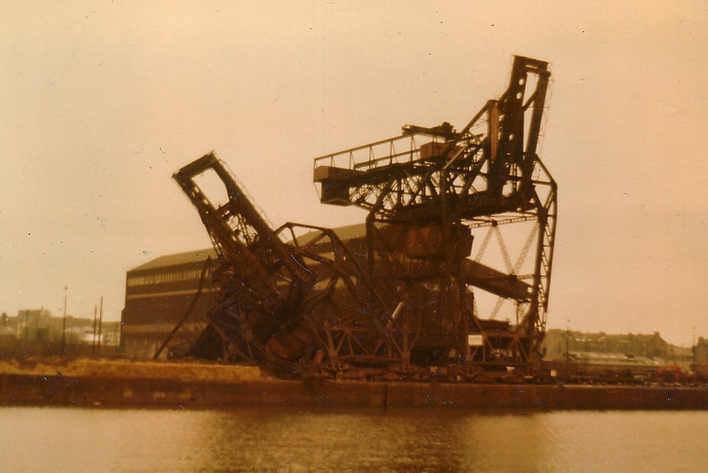 By the 1970s proposals to build a new deepwater ore and oil terminal were being considered - three possible locations were the Ardmore peninsula near Cardross, Wemyss Bay and Hunterston. The Ardmore proposal would have involved construction of a 8,500 foot long jetty that would have stretched from the shore near Craigendoran to the deepwater off Roseneath Point. Eventually it was decided to build an ore and coal terminal at Hunterston where the length of the required jetty would be 4,500 feet. The facility opened in June 1979 and General Terminus closed. The three giant Arrol-built cranes survived for another 18 months then they were demolished by explosive charges. This picture was taken on 6th January 1981 when the easternmost of the three 100 ft high sister unloaders was reduced to a heap of tangled metal by the explosion of charges in its two upstream support legs. Note: by this time the dual ore conveyor belt had already been dismantled and demolition of the big ore storage silo building had commenced