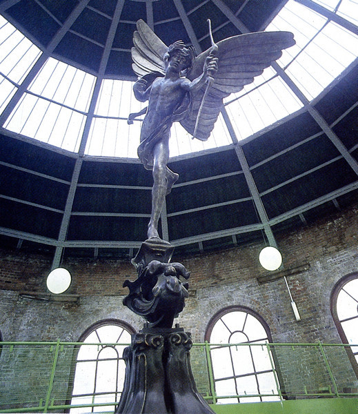 "The only other former dock building that survived to be included in the Festival was the South Rotunda of the former Glasgow Harbour tunnel. During the Festival the refurbished building was utilised as a cafe / bar (run by the well known Nardini family of Largs) with this large statue of Eros (a replica of the one at Piccadilly Circus in London) as its centrepiece.<br /> <br /> Opened in 1895 by the Glasgow Harbour Tunnel Company it passed under the Clyde from Tunnel Street, Finnieston on the north bank to Mavisbank Quay at Plantation Place on the south side of the river. It consisted of a passenger tunnel and two vehicle tunnels accessed by hydraulic hoists housed within the north and south Rotunda buildings.   Horses and carts descended on the hoists for the journey under the Clyde. In 1926, the tunnels and their red brick rotundas were taken over by Glasgow Corporation. A water main with a diameter of 914.4mm was installed in the pedestrian tunnel in 1938.<br /> <br /> A picture of the tunnel in its heyday with horse drawn vehicles can be seen at the excellent VirtualMitchell website (compiled by the Mitchell Library, Glasgow) - follow this link:<br /> <a href=""http://www.mitchelllibrary.org/virtualmitchell/image.php?i=14212&r=2&t=4&x=1"">http://www.mitchelllibrary.org/virtualmitchell/image.php?i=14212&r=2&t=4&x=1</a><br /> <br /> The pedestrian tunnel was closed by the 1930s but pedestrians continued to use the vehicle tunnels. It is commonly stated that the vehicle tunnels were closed in 1943 some people dispute that fact and recall seeing vehicles using the tunnels in the 1950s. It seems that the pedestrian tunnel was reopened in the 1940s and it continued in use until 1980. The vehicle tunnels were sealed in 1986.<br /> <br /> A lone walk through the Harbour Tunnel was not for the faint hearted, a 3ft water main ran along one side with various indeterminate noises nearby and the sparse illumination by bare light bulbs did little to reassure. A picture of the tunnel taken by a member of the Partick Camera Club in 1955 can be studied at the following link:<br /> <br /> <a href=""http://www.theglasgowstory.com/imageview.php?inum=TGSE01300&PHPSESSID=3a0df405a536b3a238c7d6ef548d809f"">http://www.theglasgowstory.com/imageview.php?inum=TGSE01300&PHPSESSID=3a0df405a536b3a238c7d6ef548d809f</a><br /> <br /> <br /> <br /> Although earmarked for closure, the tunnel, like the Clyde ferries, was reprieved during the modernisation of the Subway in the late 70s but finally closed in 1980. <br /> <br /> Due to the presence of the water main the pedestrian tunnel was not sealed. This tunnel is now owned by Scottish Water, known as the Finnieston Tunnel and operates solely to access the water main."
