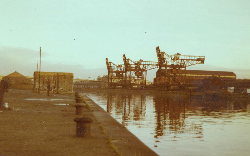 "A view of General Terminus Quay from Finnieston Quay at the end of 1980 and just before demolition of the ore terminal began. The large rectangular stone block on Finnieston Quay was the base of the former steam-powered Finnieston Crane. It was built in 1893 by Cowans Sheldon of Carlisle. A sister crane was built on the west wall of the canting basin of the new Princes Dock in 1895. Both cranes had a maximum lift capability of 130 tons, the largest on the Clyde at the time. The Finnieston and Princes Dock heavy lift cranes, together with another 60 ton crane at Berth No 81 on Plantation Quay were utilised to lift many of the large heavy engineering products of Clydeside aboard ships for export. Principal among these were steam locomotives of which 24,000 were built at the four big works in Springburn and Queens Park. They were also used to lift engines and boilers aboard new ships built on the river when the builder did not have their own heavy lift facilities. <br /> <br /> The 175-ton Stobcross Crane (often incorrectly called the Finnieston Crane) was built in 1932 to replace the Finnieston Crane as there was a plan to build a high level bridge across the river at Finnieston Street. In fact that bridge was not built and the Finnieston Crane continued to work with the nearby Stobcross Crane until the 1960s. With the closure of the North Britiah Locomotive Works and many of the Clyde shipyards in the 1960s, the Finnieston, Princes Dock and Plantation heavy lift cranes were demolished and any large loads were handled by the Stobcross Crane.<br /> <br /> A 1930s view of the 130 ton Finnieston crane can be seen at the following link. The picture is taken from the temporary crane erected to enable the construction of the new Stobcross Crane, the tower of which can be seen in the bottom left corner. The Finnieston crane is working with a vessel alongside. Also in the view is the Lancefield Quay - Mavisbank Quay elevating deck vehicular ferryboat. The works in the middle left of the picture are the marine engine building works of David Elder & Co, Harland & Wolff and Barclay Curle where many of the engines lifted by the cranes were built<br /> <br />  <a href=""http://www.mitchelllibrary.org/virtualmitchell/image.php?i=15508&r=2&t=4&x=1"">http://www.mitchelllibrary.org/virtualmitchell/image.php?i=15508&r=2&t=4&x=1</a><br /> <br /> The following link has a similar but closer view of the Finnieston Crane in the mid 1950s when the General Terminus unloaders were being erected and the depth of water at the quay was being increased<br /> <br />  <a href=""http://www.mitchelllibrary.org/virtualmitchell/image.php?i=14554&r=2&t=4&x=1"">http://www.mitchelllibrary.org/virtualmitchell/image.php?i=14554&r=2&t=4&x=1</a><br /> <br /> Note: Previous to the establishment of the two 130 ton cranes at Finnieston and Princes Dock the Clyde Trust had provided a 50-ton fitting out crane at Finnieston and a 75 ton fitting out crane at Stobcross."