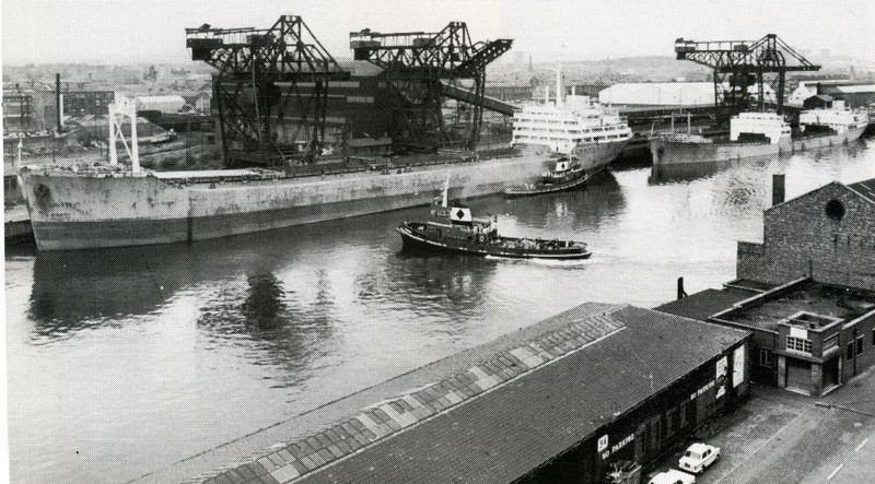 """In December 1954 the Clyde Trustees approved a proposal by Lanarkshire steelmakers David Colville & Co to convert General Terminus Quay into an ore discharging facility capable of handling two 530-foot long, 16,000-ton ore ships. The Glasgow cranebuilders Sir William Arrol & Company supplied three giant ore unloaders which dominated the Central Glasgow skyline for the next quarter of a century. The new ore terminal opened for business in 1957. This picture shows General Terminus operating at its peak capability with the bulk carriers Cape Howe and Cape Franklin alongside. Both of these ships were built by the Port Glasgow shipbuilder Lithgows Ltd for the Lyle Shipping Company of Glasgow and they were regular visitors to the Terminus. See details of the vessels at:<br /> <br />  <a href=""""http://www.clydesite.co.uk/clydebuilt/viewship.asp?id=18450"""">http://www.clydesite.co.uk/clydebuilt/viewship.asp?id=18450</a><br /> <br /> and<br /> <br />  <a href=""""http://www.clydesite.co.uk/clydebuilt/viewship.asp?id=18460"""">http://www.clydesite.co.uk/clydebuilt/viewship.asp?id=18460</a><br /> <br /> A long conveyor belt, running the length of the quay, carried the discharged ore over the public roadway to a 14,000 ton capacity covered bunker from which it was discharged, via two intermediate weigh cars, into the railway wagons. The storage bunker is in the large black building behind the nearest two unloaders. It can be seen in more detail at the following SCRAN website link (Note: a SCRAN subscription is required to see full size pictures there, otherwise you will see a thumbnail version):<br /> <br />  <a href=""""http://www.scran.ac.uk/database/record.php?usi=000-000-188-493-C&PHPSESSID=3ki10odvdk69tmh3ilrnvg89r2&scache=22it6170lk&searchdb=scran"""">http://www.scran.ac.uk/database/record.php?usi=000-000-188-493-C&PHPSESSID=3ki10odvdk69tmh3ilrnvg89r2&scache=22it6170lk&searchdb=scran</a><br /> <br />  The following picture at the SCRAN website show the west end of the site where the qua"""