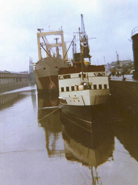 """This view is looking east along the original south wall of the canting and south basins of Princes Dock in May 1973. By this time the dock was little used by commercial shipping except for some heavy lift shipments from the west wall of the canting basin. <br /> <br /> The large vessel at the south wall in this view is the new cargo ship Orli, built by Upper Clyde Shipbuilders (ex John Brown, Clydebank) for the Haverton Shipping Company. She had moved to the Princes Dock to complete her outfitting following the collapse of UCS<br /> <br />  <a href=""""http://www.clydesite.co.uk/clydebuilt/viewship.asp?id=656"""">http://www.clydesite.co.uk/clydebuilt/viewship.asp?id=656</a><br /> <br /> The smaller vessel was the Clyde excursion steamer Queen Mary II. This vessel had been built at the famous shipyard of William Denny & Brothers at Dumbarton in 1933 for the long running excursion services from Glasgow Bridge Wharf to the Clyde coast. These services had been withdrawn in 1969 after which the turbine steamer concentrated on services on the Firth of Clyde. On this occasion, on charter to the enthusiasts' Clyde River Steamer Club , the vessel had returned to Glasgow for a special sailing to commemorate her 40th Anniversary. As her traditional berth was no longer available the vessel berthed in the Princes Dock.<br /> <br />  <a href=""""http://www.clydesite.co.uk/clydebuilt/viewship.asp?id=11562"""">http://www.clydesite.co.uk/clydebuilt/viewship.asp?id=11562</a>"""