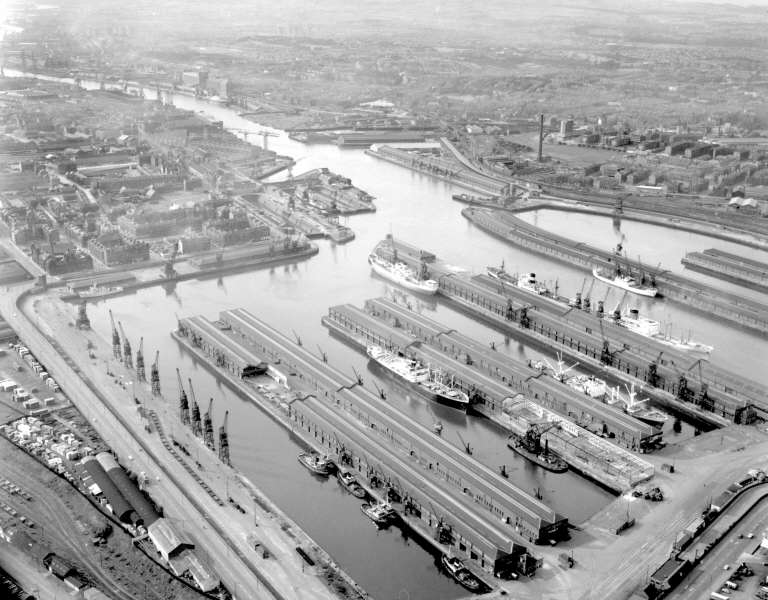 """A view of the Prince's Dock from the south-east. By the time that this photo was taken the coal wagon hoist had been removed and replaced by another heavy lift crane which can be seen at the far end of the minerals quay <br /> <br /> For some years the tugs working in Glasgow harbour were based at the east end of the south basin.<br /> <br /> Also in this view the only floating crane owned by the Clyde Navigation Trust, the Newshot, can be seen berthed near the east end of the Centre Basin. The picture at this SCRAN link shows the Newshot delivering a container of export Ballantines Scotch Whisky to the vessel Pacific Strong in the North Basin of the dock<br /> <br />  <a href=""""http://www.scran.ac.uk/database/record.php?usi=000-000-036-380&PHPSESSID=luh9re8912mujo2ft1stqlpos1&scache=43ev88osw9&searchdb=scran"""">http://www.scran.ac.uk/database/record.php?usi=000-000-036-380&PHPSESSID=luh9re8912mujo2ft1stqlpos1&scache=43ev88osw9&searchdb=scran</a><br /> <br /> An earlier view, when the dock was much busier can be studied at the following link - looking along the south basin from the east end of the dock with Govan Town Hall at the far end<br /> <br />  <a href=""""http://www.mitchelllibrary.org/virtualmitchell/image.php?i=16402&r=2&t=4&x=1"""">http://www.mitchelllibrary.org/virtualmitchell/image.php?i=16402&r=2&t=4&x=1</a>"""